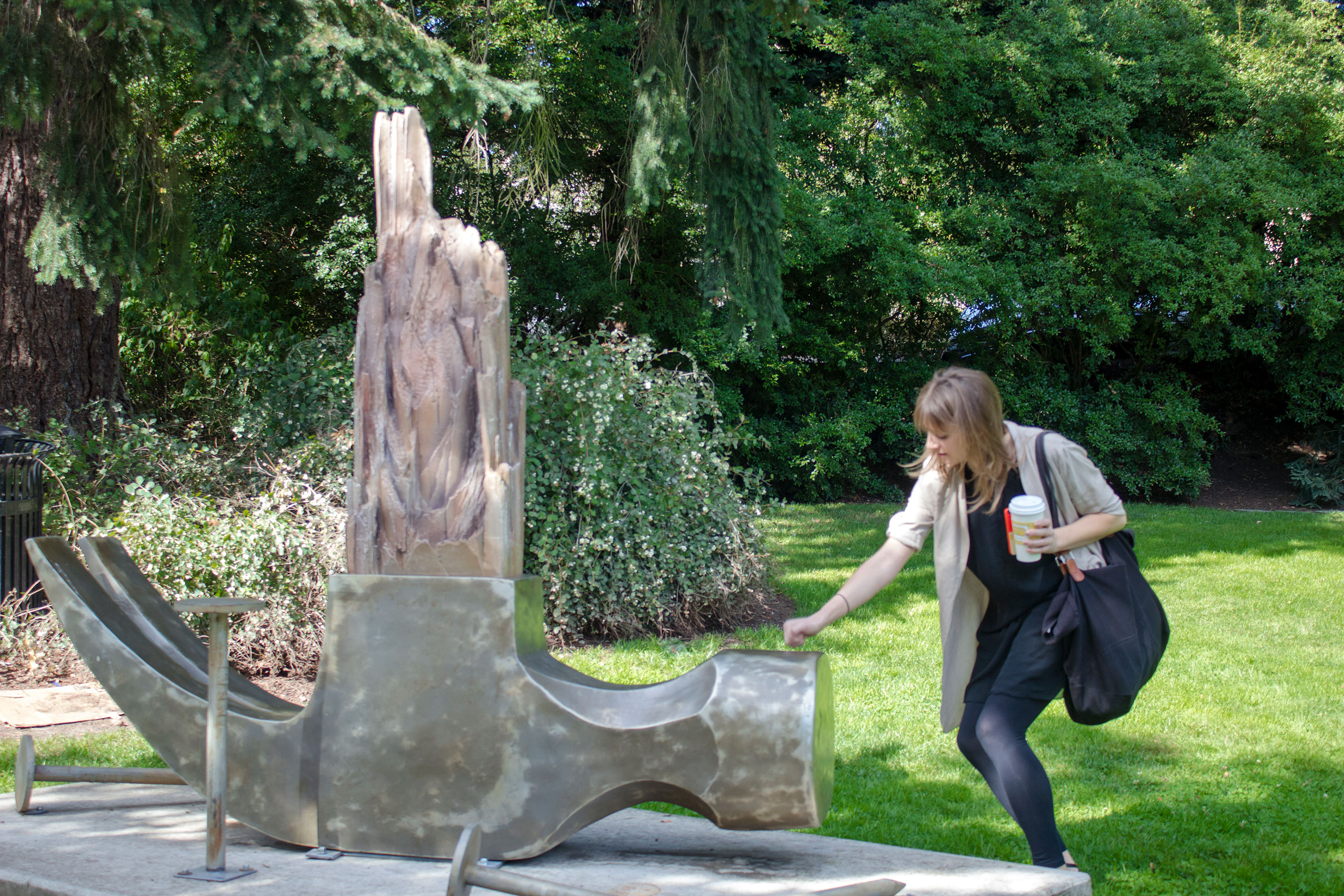 Female knocks on giant upside down metal hammer sculpture with broken wood handle and oversize nails in Lake Oswego park