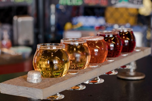 Multi-colored ciders from light to dark on a diagonal taster tray at 12 Bridge Ciderworks in Oregon City in Oregon's Mt. Hood Territory