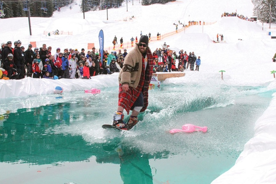 Snowboarder goes all out trying to glide his board across freezing water at the pond skimming competition during Mt. Hood Skibowl's end of season Snow Beach Festival