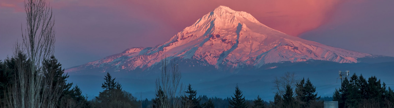 The fading sun shines on the peak of Mt Hood as the rest of the mountain and surrounding sky are bathed in pink alpenglow in Oregon's Mt. Hood Territory