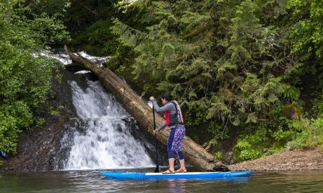 Woman paddleboarding near a waterfall on Estacada Lake Clackamas River