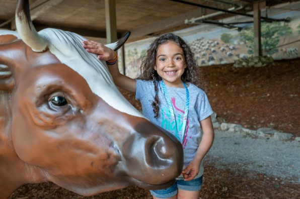 Girl smiling next to a model Oxen at the End of the Oregon Trail