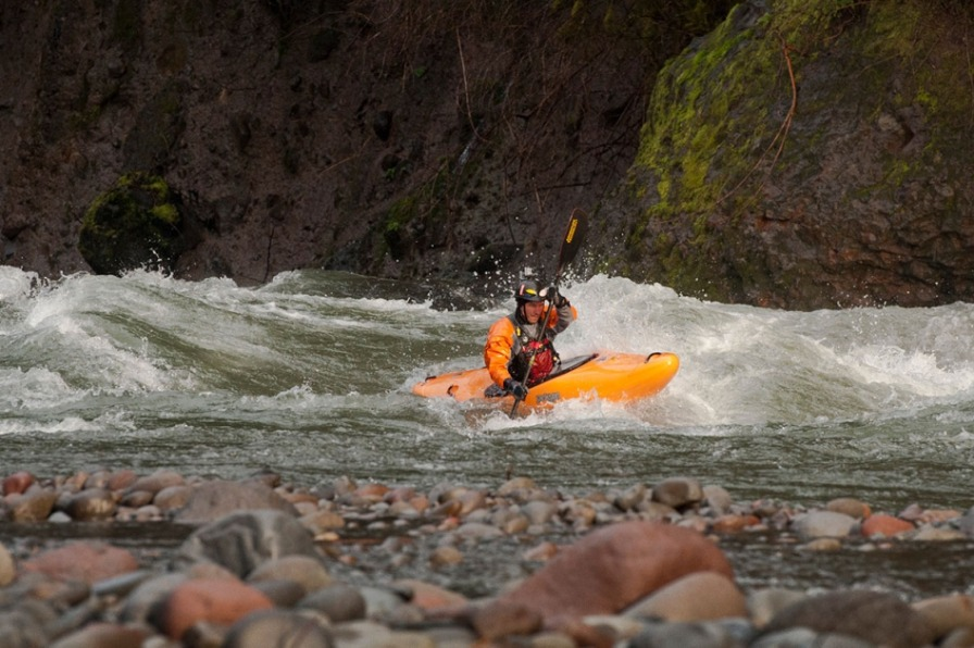 Kayaker on an eNRG Kayaking tour shoots the whitewater rapids on the Sandy River