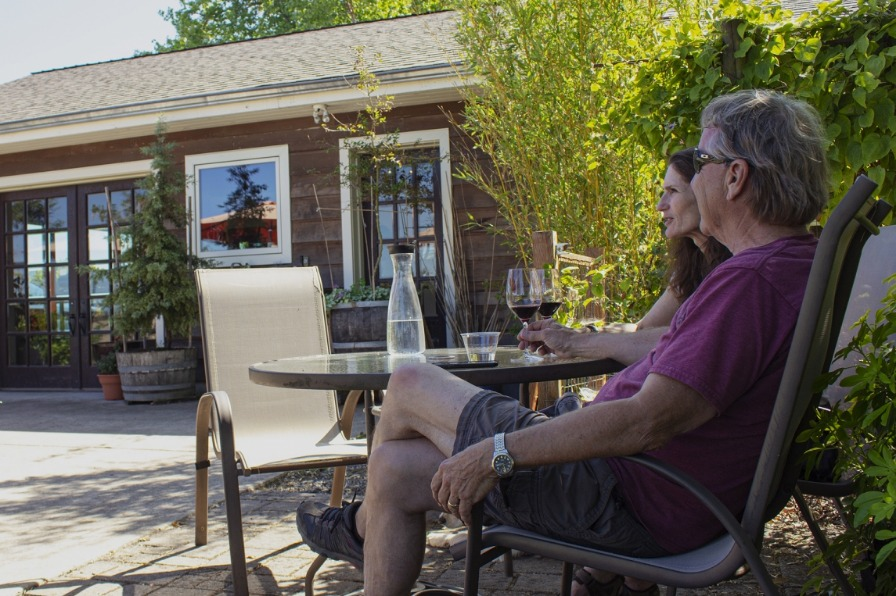 Couple enjoying wine on the patio at Alexeli Winery