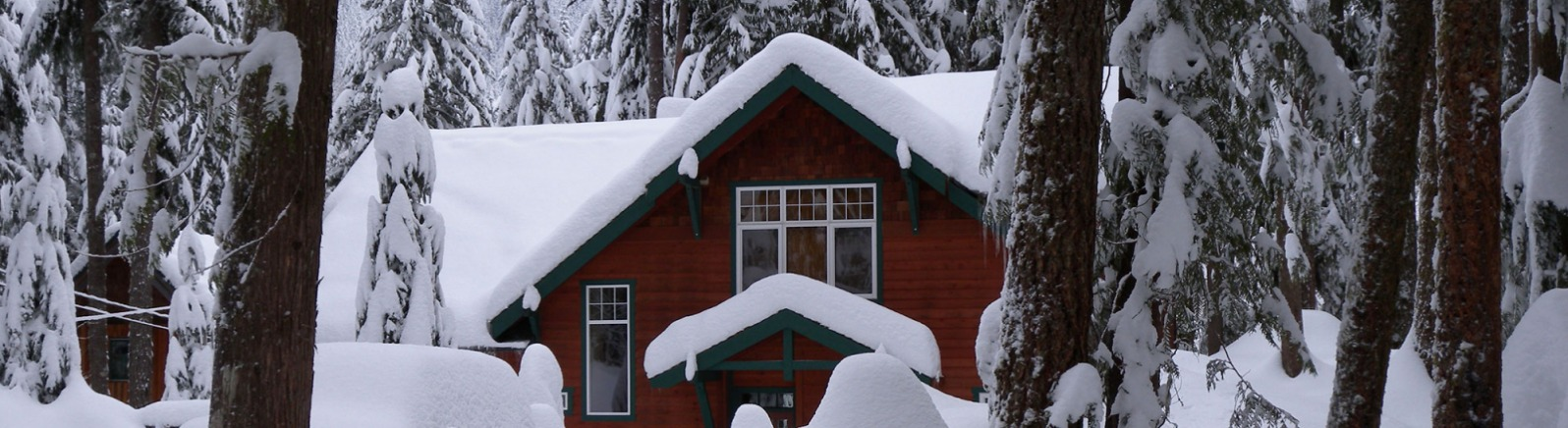 Deep, deep snow covers the roof of the cozy red rental cabin, SUV and forest floor deep in the Mt. Hood National Forest