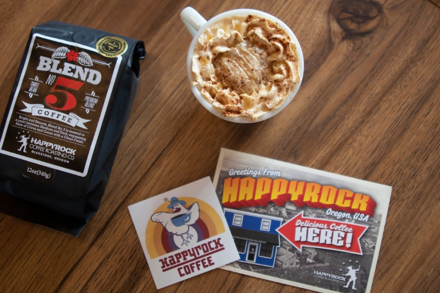 Happyrock Coffee Roasting Co. display of a made coffee, bag of coffee beans and stickers