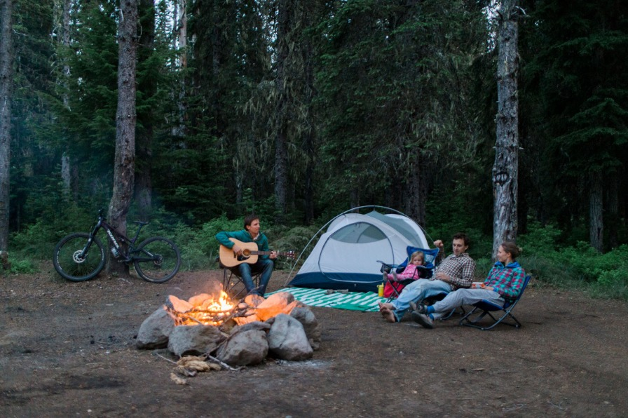 Campers enjoy guitar music as they sit around the campfire
