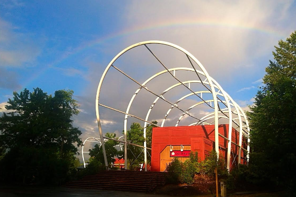 A rainbow arcs over the End of the Oregon Trail Interpretive Center building and the white metal covered wagon bonnet frame