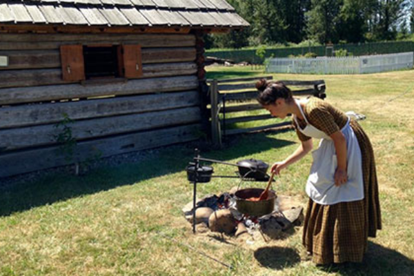 Young woman dressed in long pioneer dress and apron stirs food cooking in cast iron dutch oven over an open fire