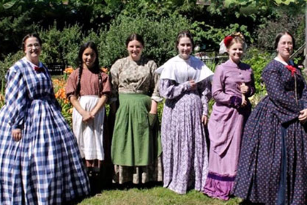 6 pioneer women reenactors dressed in their finest gingham checkered and floral pattern dresses pose in the farm's garden