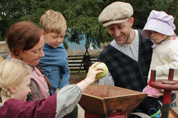 Reenactors as pioneer parents and their 3 small children feed an apple into cider press at Philip Foster Farm's Cider Squeeze