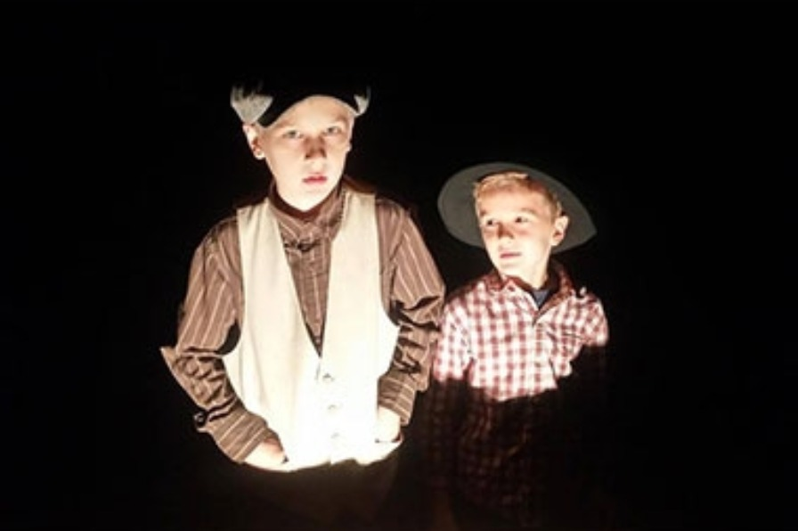 Two young boys in pioneer era clothing showcased in eerie lighting volunteer at Haunted Farm event at Philip Foster Farm