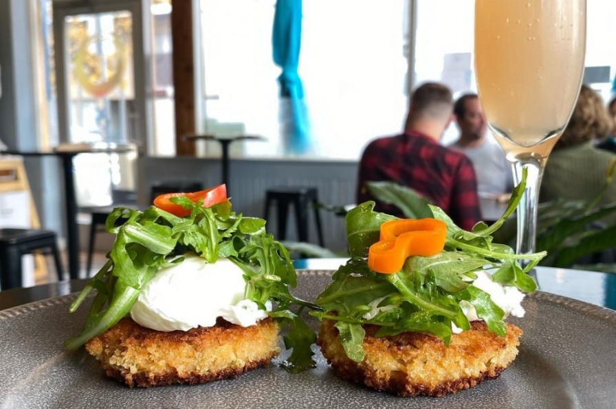 crab cakes stacked with fluffy egg whites, arugula and bell pepper in the foreground with Ovation Bistro diners in the background