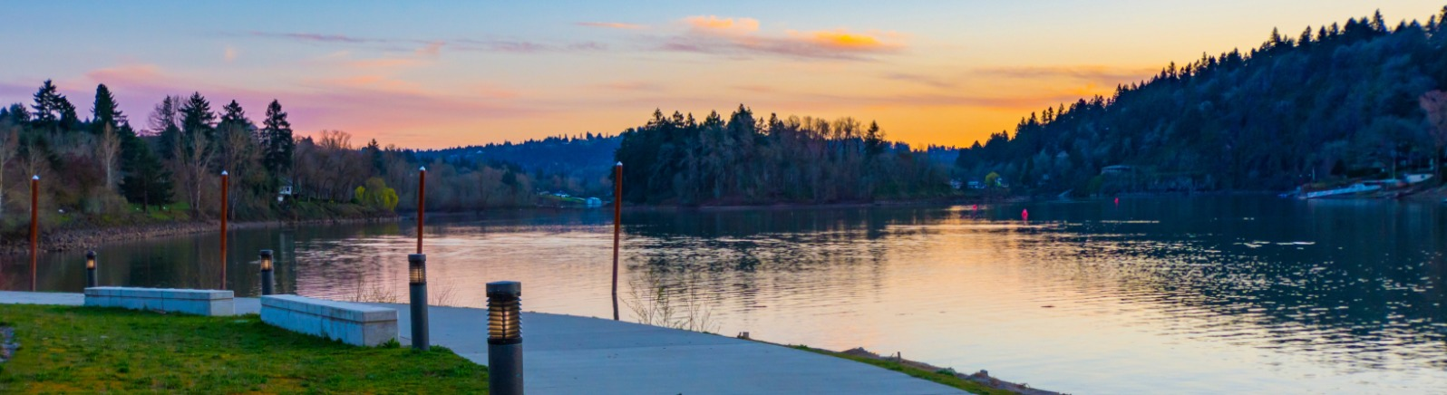 view of a paved path alongside the Willamette River with a pink and orange sunset going behind trees in the background