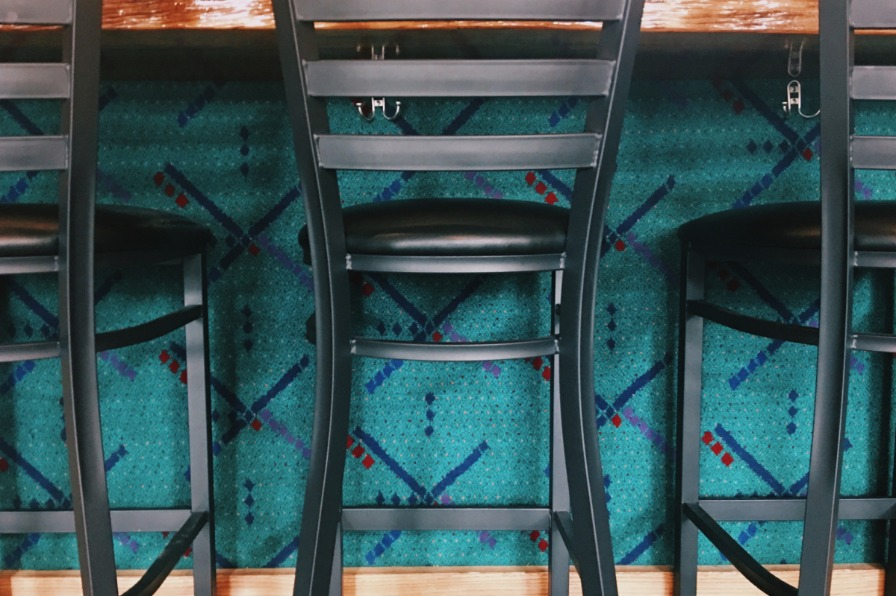old PDX airport carpet decorates a bar front with several bar seats in front