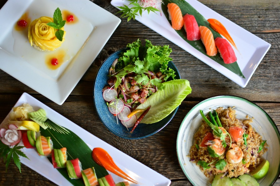 bird's eye view of various sushi and Thai dishes displayed on a wood table