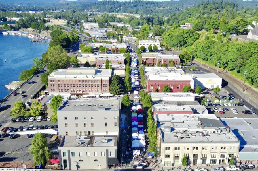 aerial view of downtown Oregon City's brick and stucco buildings with the Willamette River on their left side