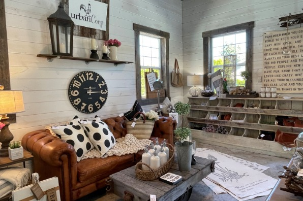 country chic store display looks like someones living room with a leather sofa and reclaimed wood coffee table