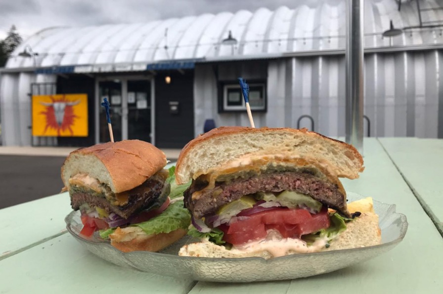 a cheeseburger cut in half sits on a light green picnic table in front of a Quonset hut, Clay's Smokehouse Grill