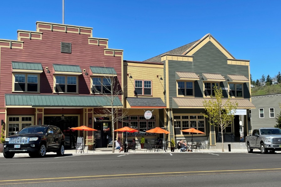 view from across the street of Main Street building exteriors and tables with orange umbrellas in front