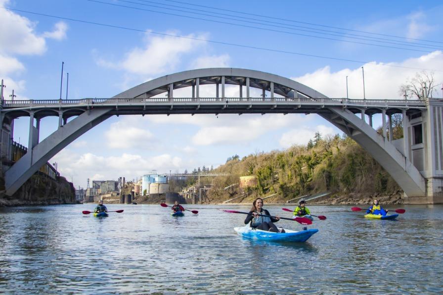 Kayakers paddling under arch bridge willamette river