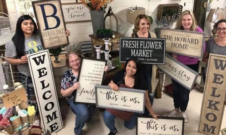 Class from sign making workshop holding their signs at The Rustic Shed in Molalla