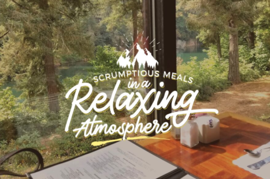 """A table near the window at The Cazadero Steakhouse in Estacada. Text overlay reads """"scrumptious meals in a relaxing atmosphere"""""""