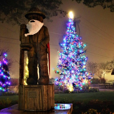 Estacadas iconic logger statue decorated for Christmas with a lighted tree in the background