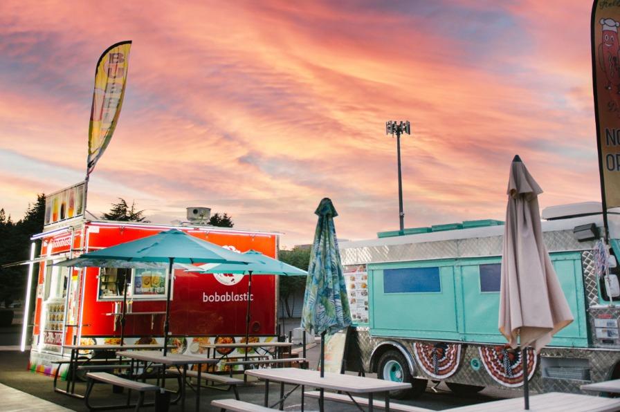 Pink sky over the Lumberyard Food Cart pod food trucks and picnic tables in Estacada