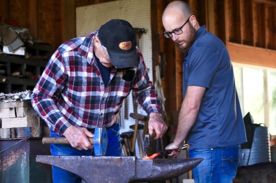 Master blacksmith and helper shape a hot metal piece into a Red Pig Garden Tool using sledgehammer on large anvil