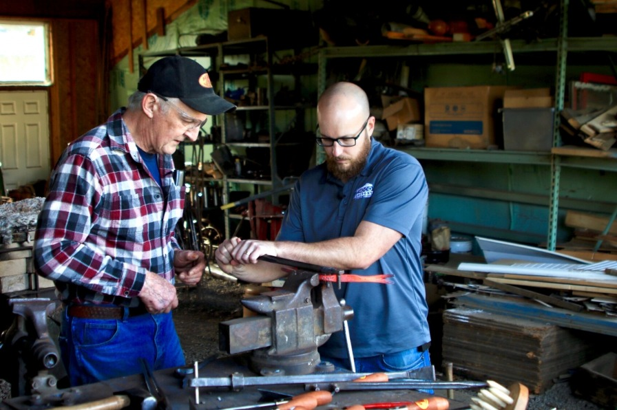 Blacksmith and assistant bend hot metal in vise to make a weeder at Red Pig Garden Tools in Oregon's Mt. Hood Territory