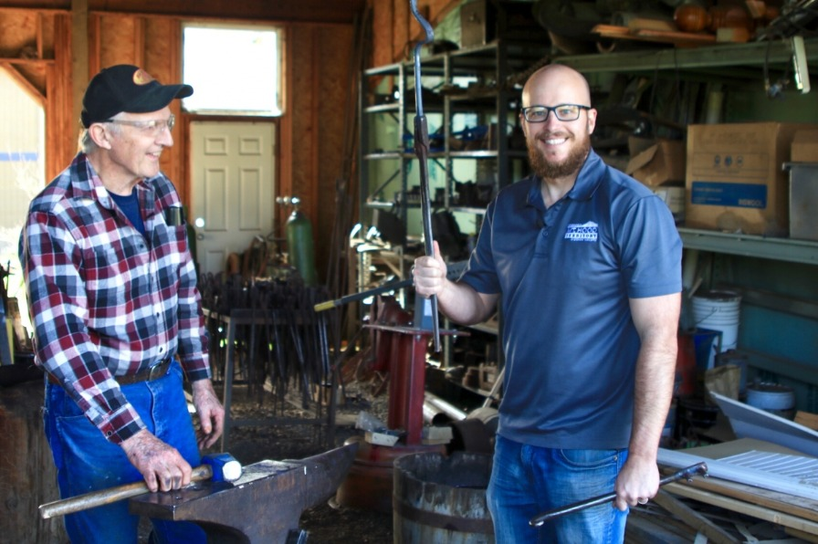 Worker shows off the weeding tool he just made on the forge and anvil in blacksmtih shop at Red Pig Garden Tools