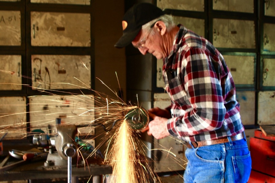Sparks fly form the grinder as balcksmith grinds down edges of a Red Pig Garden Tool