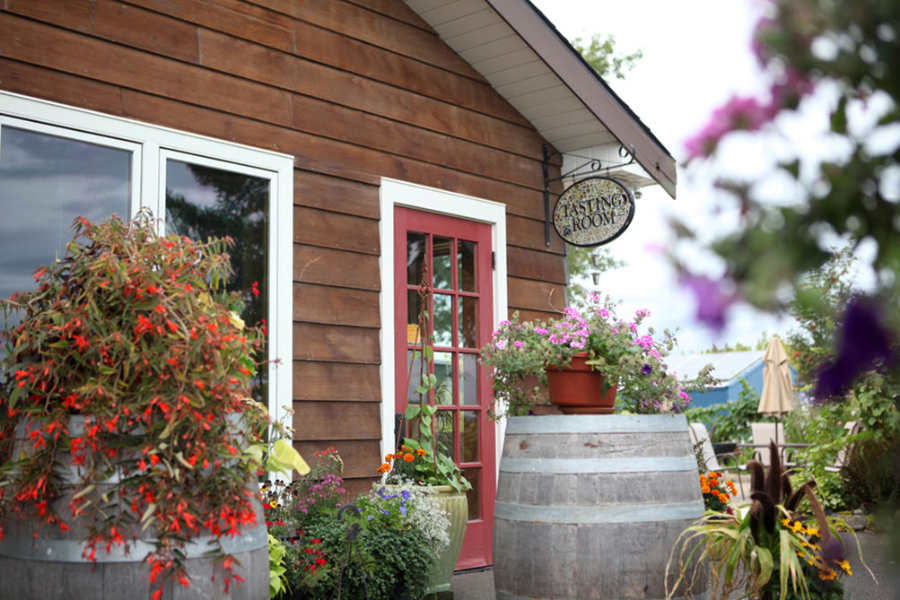 Orange and pink flowers perched atop two wine barrels with other colorful flowers surround the door of Alexeli's tasting room