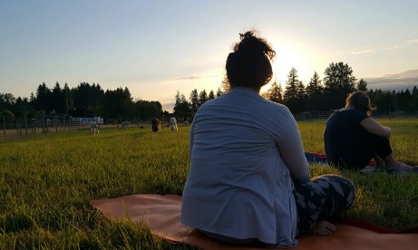 Two yoga class members sit in the middle of the pasture looking at alpacas in the distance as sun sets over Cascade foothills