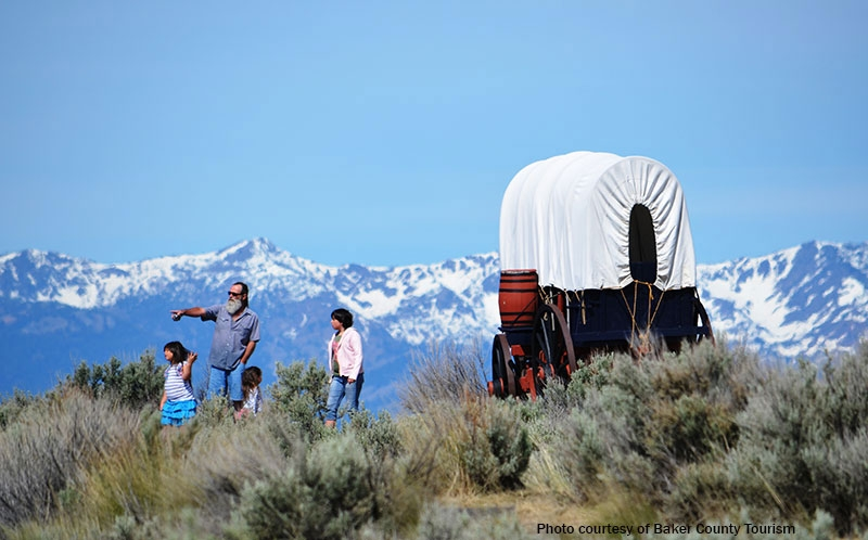 Mountains in the background of a family exploring the Oregon Trail with a wagon replica.