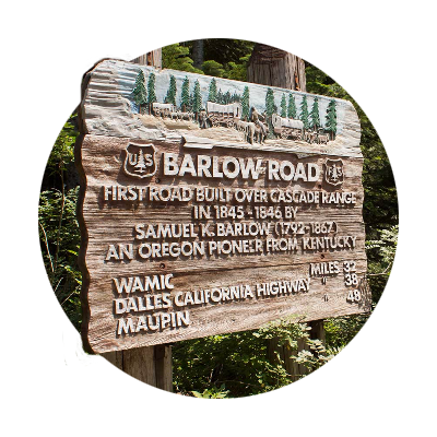Wooden directional sign at Barlow Pass with a wagon train scene, Barlow road info and mileages to Wamic, Dalles and Maupin
