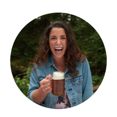 Long dark-haired young woman is laughing heartily as she holds her foamy headed mug of beer and shows off her beer mustache.
