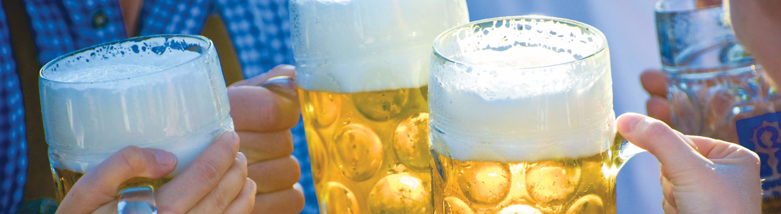 Close-up of hands holding three large glass mugs of golden beer with frothy heads of foam and making a toast among friends