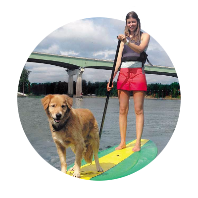 Young woman paddles her stand up paddleboard with her golden retriever along for the ride on the Willamette River