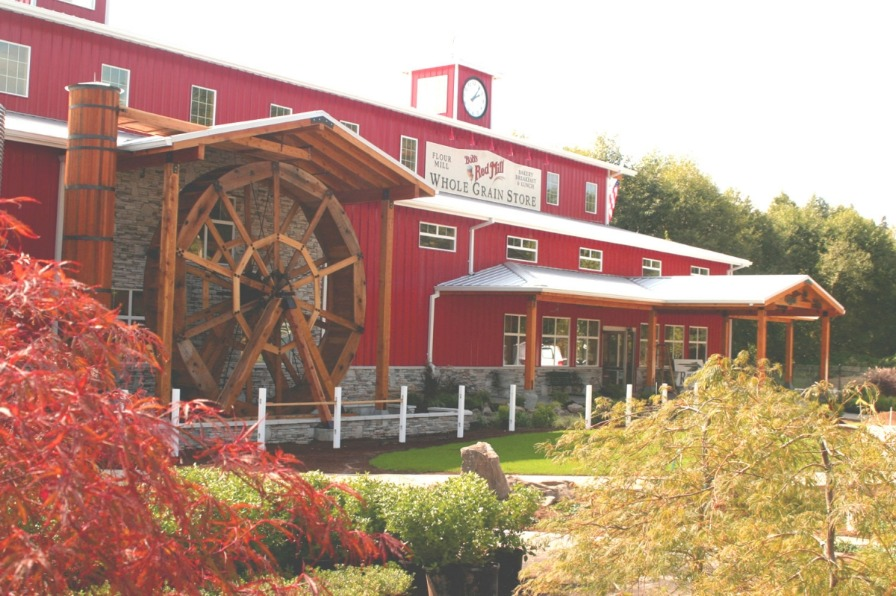Red exterior of Bob's Red Mill Store with clock atop roof and its large wooden waterwheel near covered front entrance