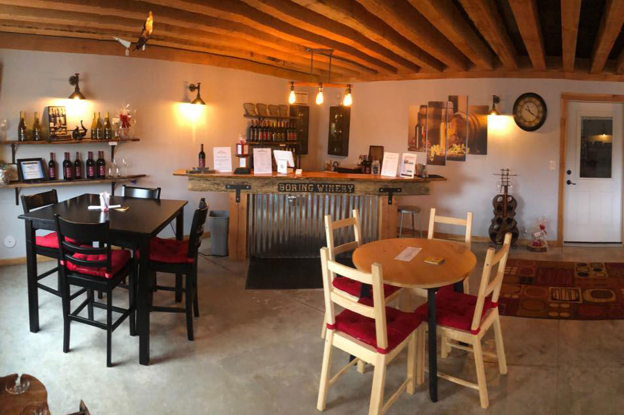 Panoramic view of Boring Winery's tasting room interior with low beam ceiling, black and natural wood tables and serving bars