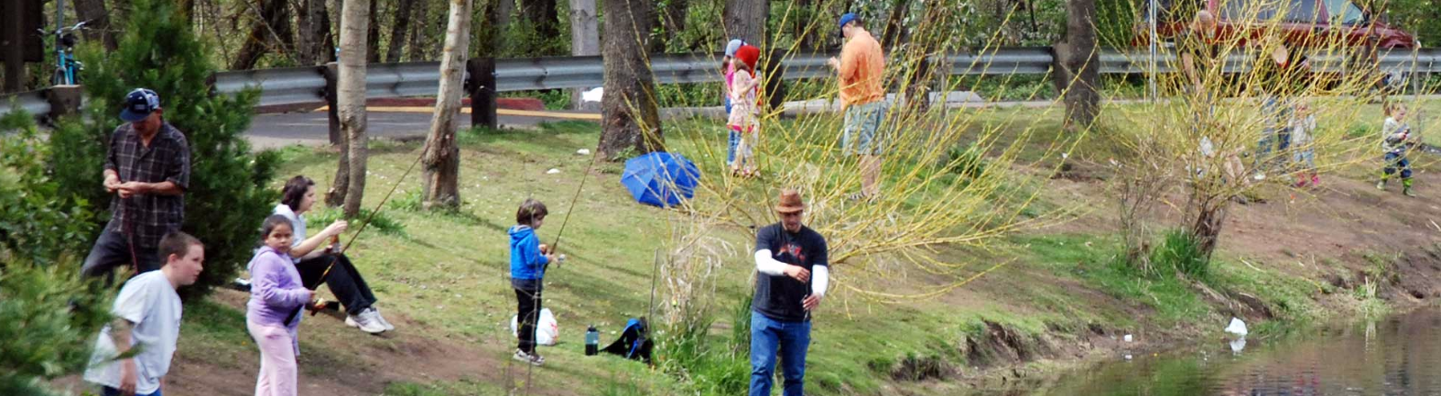 Children and parents with their fishing poles at the Canby Community Park fishing pond in Oregon's Mt. Hood Territory