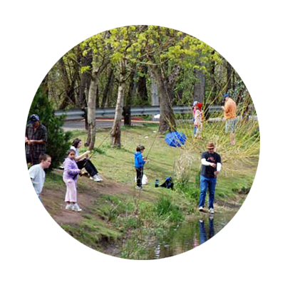 Circular photo of parents helping kids fishfrom the water's edge at the Canby Community Park fishing pond