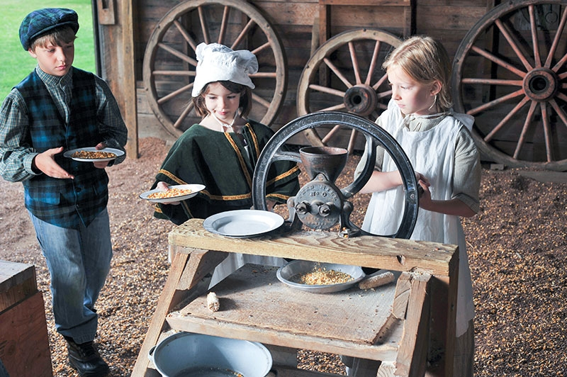Two young girls and a boy in pioneer era clothing grind corn in barn where wagon wheels lean on wall at Philip Foster Farm.