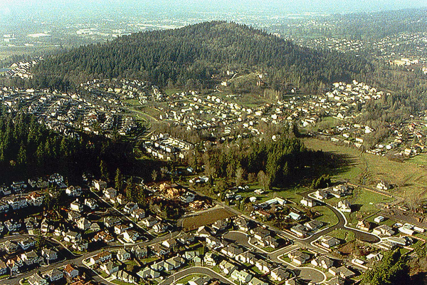 Aerial view of Happy Valley's neighborhood streets and hundreds of homes surrounding Mt. Talbert's forested butte.