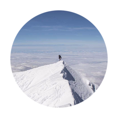 A mountain climber on Mt. Hood's snow-covered summit on a sunny day looks down at a cloud covered valley floor
