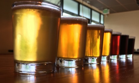 Coin Toss Brewing beer lineup of seven glasses from pale, to amber, to red, to very dark on taproom bar
