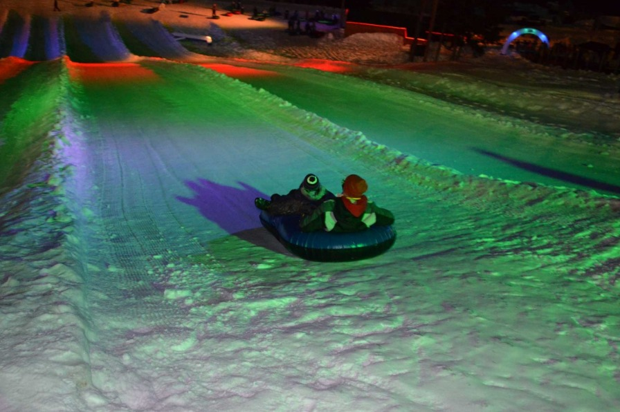 With the snow hill bathed in neon purple, green, orange and blue lights, two brave souls descend the hill on Cosmic Tubing night