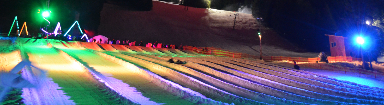 Multi-color fireworks burst into night sky over the Cosmic Tubing ski run bathed in neon lights at Mt. Hood Adventure Park